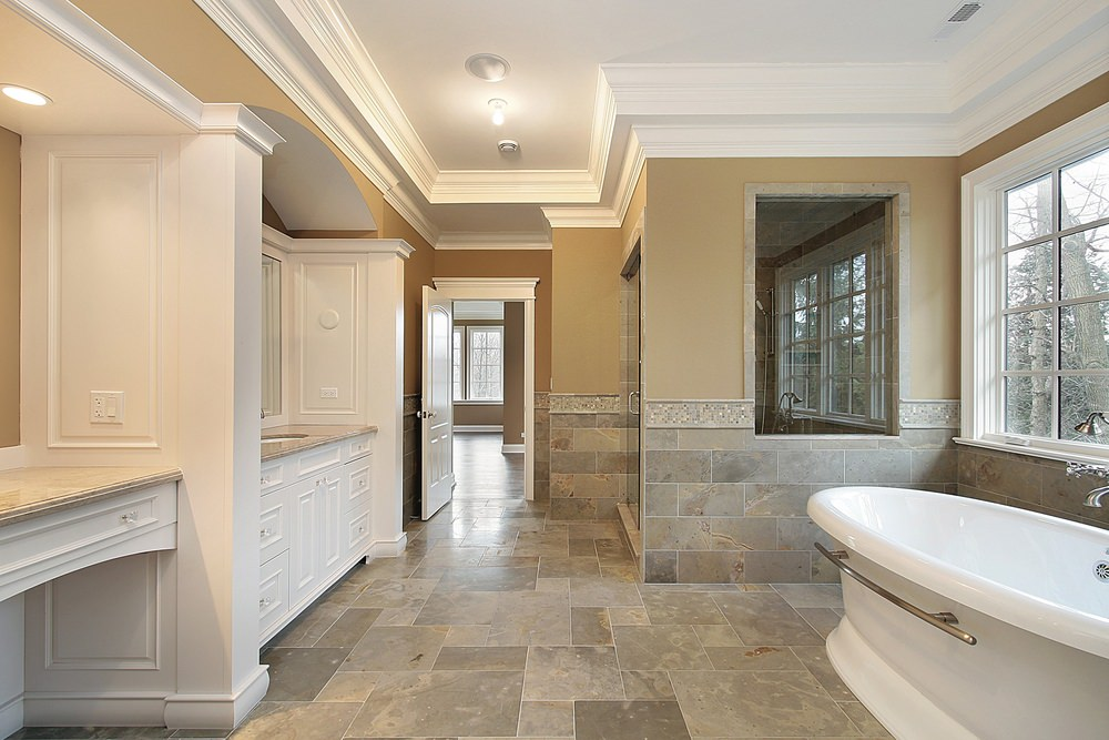 Large master bathroom featuring gray tiles flooring and beige walls. It has a large freestanding tub near the windows and a walk-in shower room.