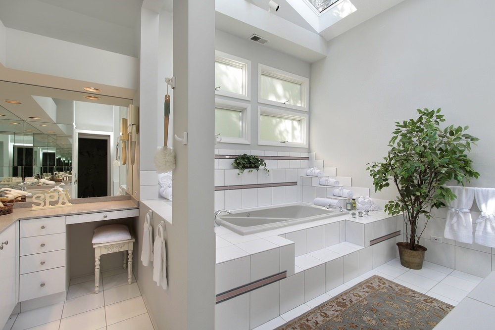 This primary bathroom boasts a small bathtub lighted by a skylight.