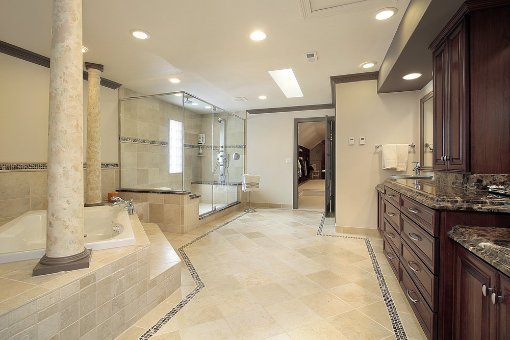 Large master bathroom featuring classy tiles flooring and ceiling lighted by recessed lights. There's a walk-in shower, a drop-in tub and elegant sink counters.
