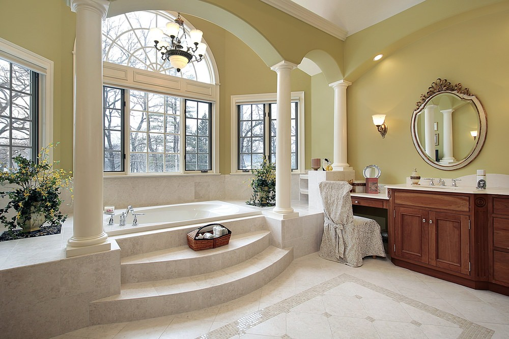 Large master bathroom with an elegant bathtub platform with Roman-style pillars and is lighted by a gorgeous chandelier.
