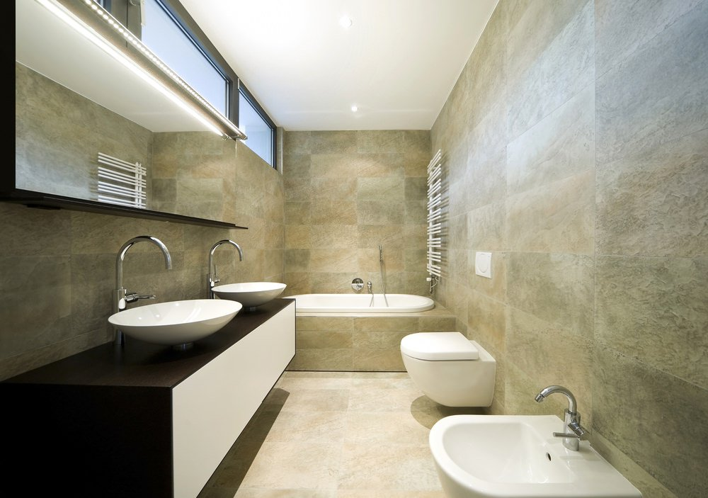 A primary bathroom that offers a corner tub and a couple of vessel sinks on a stylish floating vanity, surrounded by classy tiles walls.