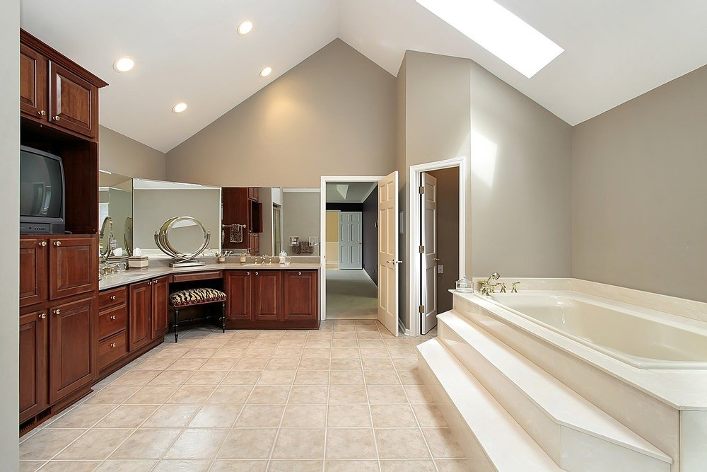 Large master bathroom with two sinks and a powder area, along with a drop-in tub under the vaulted ceiling's skylight.