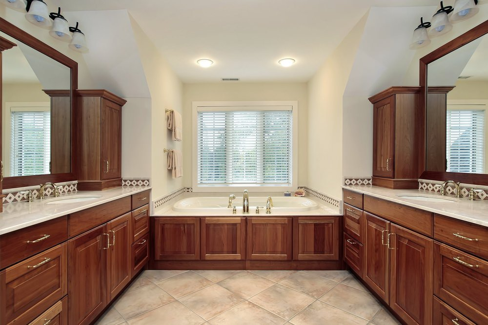 Master bathroom with cherry accent and white walls. It features a deep soaking tub near the windows. It also has two sinks.
