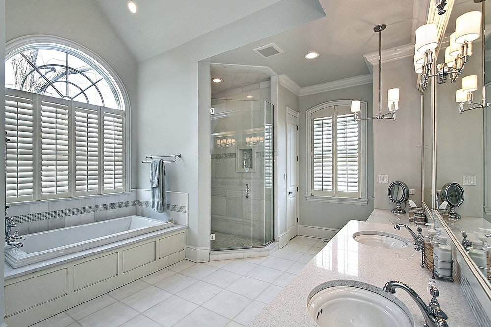 Master bathroom with gray walls and white tiles flooring. It features a double sink lighted by pendant and wall lights, and a walk-in shower along with a drop-in tub.