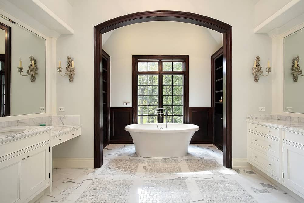 A master bathroom featuring a freestanding tub on top of the stylish marble tiles flooring. The sink counters also have marble countertops lighted by wall lights.