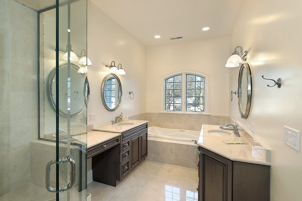 Small master bathroom offering a corner tub and a walk-in shower, along with two sink counters lighted by wall lights.