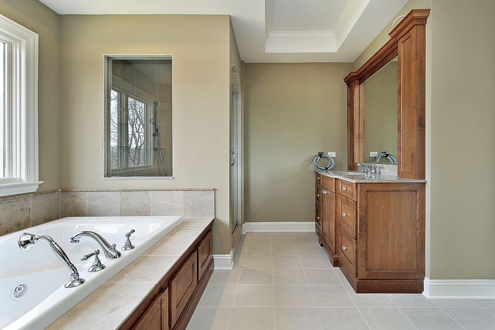 A simple master bathroom featuring tiles floors and gray walls. It also features a walk-in shower room and a large deep soaking tub.