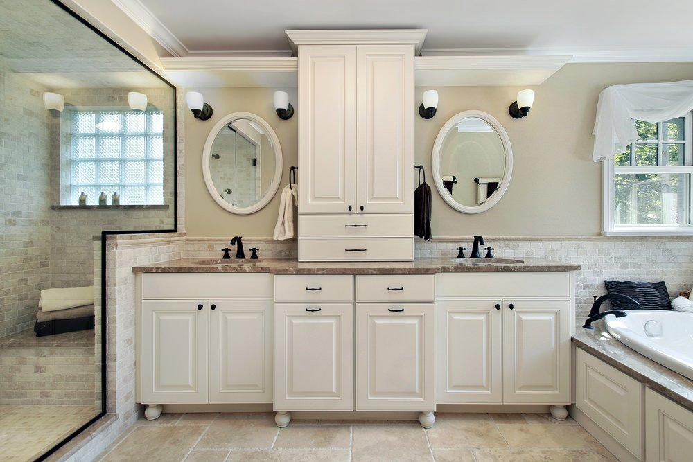 Master bathroom with a large walk-in shower room and a drop-in tub near the windows, together with a double sink counter lighted by stylish wall sconces.