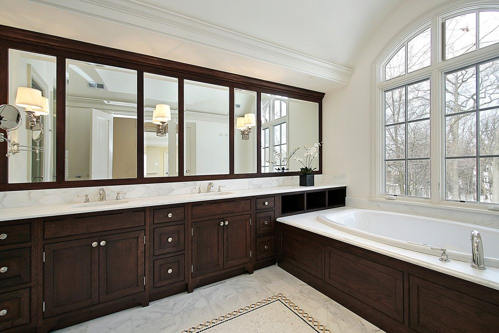 Master bathroom featuring a double sink on a marble sink counter and a large deep soaking tub set near the windows. The room has marble tiles flooring topped by a charming rug.