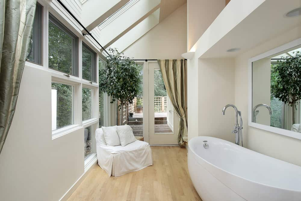 Small primary bathroom featuring a large freestanding tub and a white chair set on the hardwood flooring. The room's vaulted ceiling also features skylights.