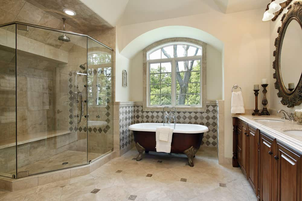 Primary bathroom with an elegant freestanding tub near the windows and a walk-in corner shower, along with a double sink under the room's tall ceiling.