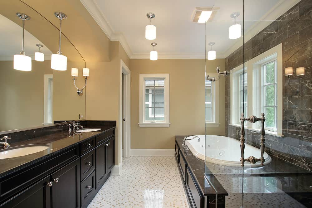 A primary bathroom featuring classy tiles floors and a stylish black double sink counter with a black marble countertop that looks absolutely elegant. The room also offers a large deep soaking tub and a walk-in shower.