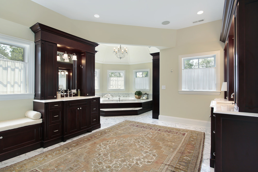 Large primary bathroom with light gray walls and marble tiles flooring topped by a massive rug. The room also offers a large corner tub near the windows.