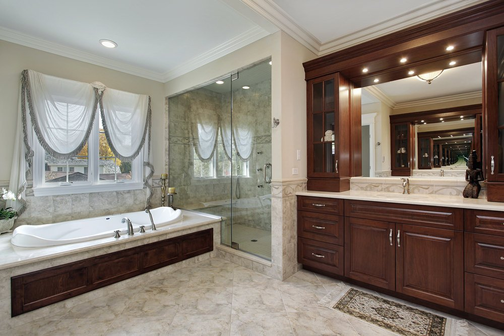 Master bathroom with marble tiles floors and a large bathtub, along with a corner walk-in shower and a lovely sink counter.