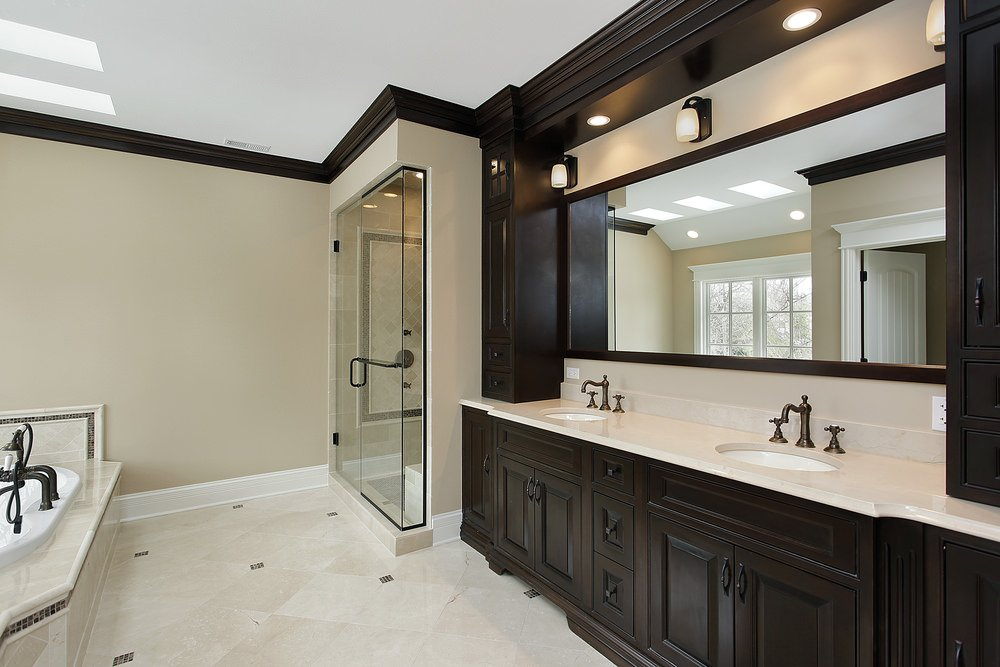 This primary bathroom boasts a double sink, a drop-in tub and a walk-in shower. The room also offers classy tiles floors and a ceiling with skylights.