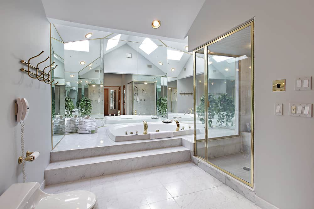 Huge primary bathroom with a stunning tall ceiling and marble tiles flooring. The room offers a deep soaking tub and a walk-in shower room.