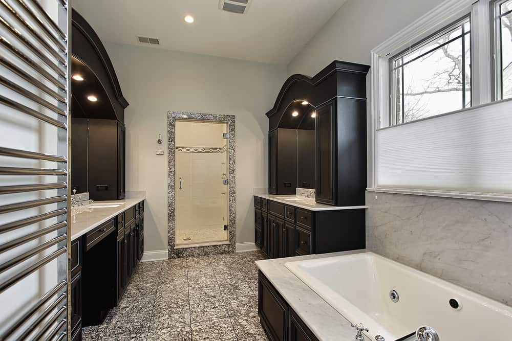 Small master bathroom featuring marble countertops on the sink counters and stunning tiles floors. There's a bathtub and a walk-in shower as well.