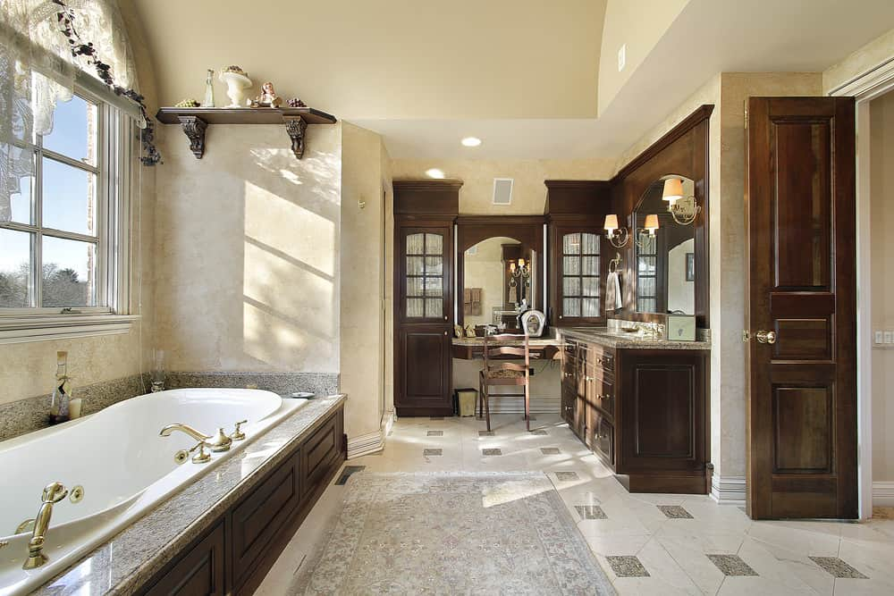 This primary bathroom offers an elegant sink counter and powder area, along with a deep soaking tub under the tall ceiling. The tiles flooring is topped by a classy rug.