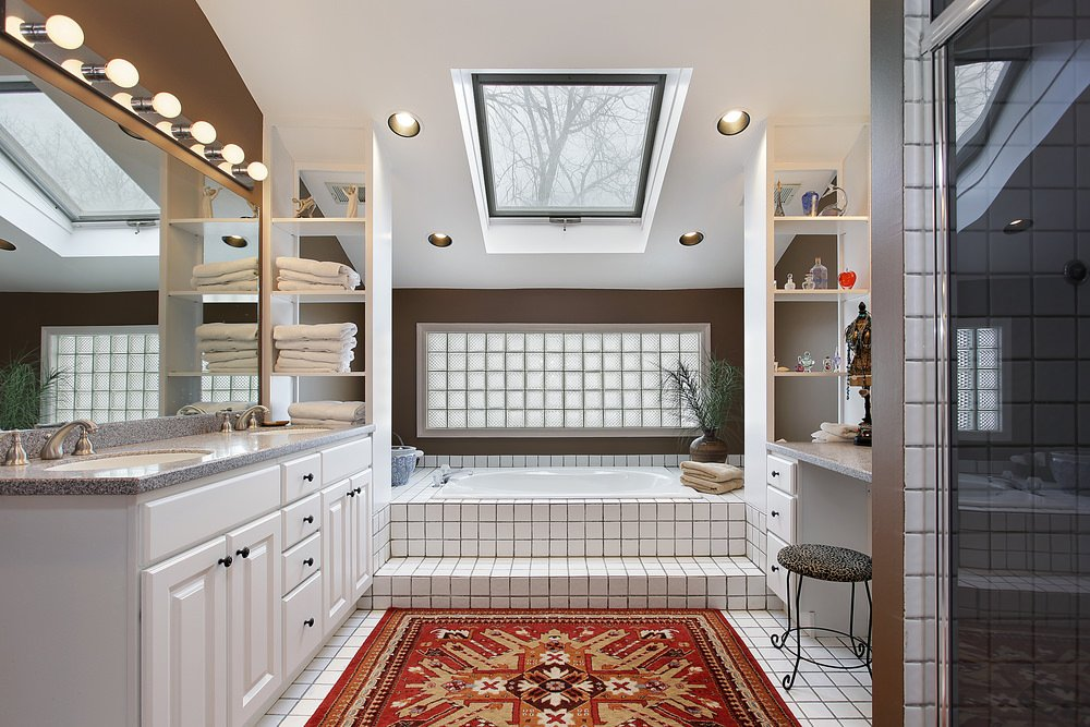 This primary bathroom boasts tiles flooring topped by a classy rug. There's a corner tub with a skylight. The double sink is lighted by wall lights.