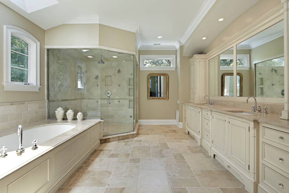 Spacious primary bathroom featuring tiles flooring and a tall ceiling. It also features two sinks, a large walk-in shower and a drop-in tub on the side.