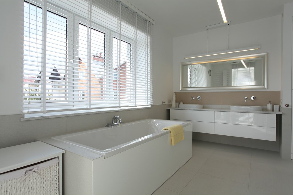 Primary bedroom featuring a large bathtub set on the tiles flooring and a floating vanity with two vessel sinks.