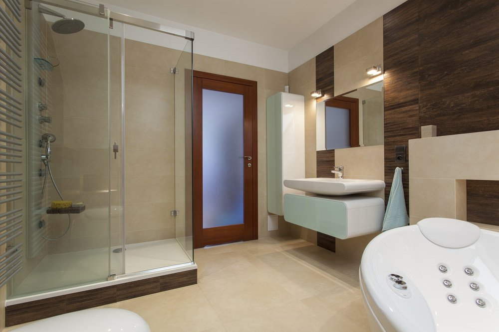 Modern primary bathroom featuring a walk-in shower and a deep soaking tub, along with a floating vanity with a large vessel sink on it.