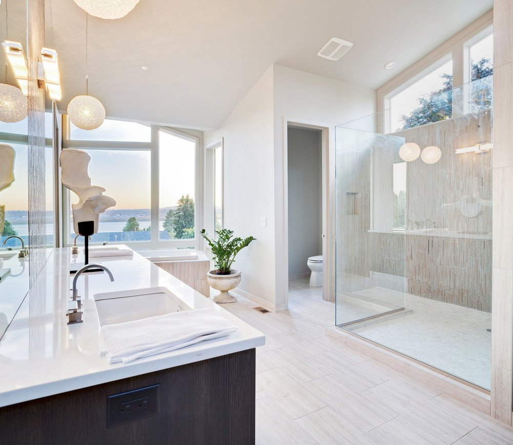 Large master bathroom boasting a large walk-in shower room and a corner tub near the glass window, overlooking the beautiful outdoor view. There's also a large bathroom counter featuring two sinks and a smooth white countertop.