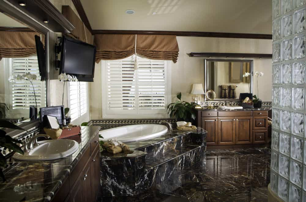 A primary bathroom boasting luxurious floors and sink counters, along with a drop-in tub and a walk-in shower.