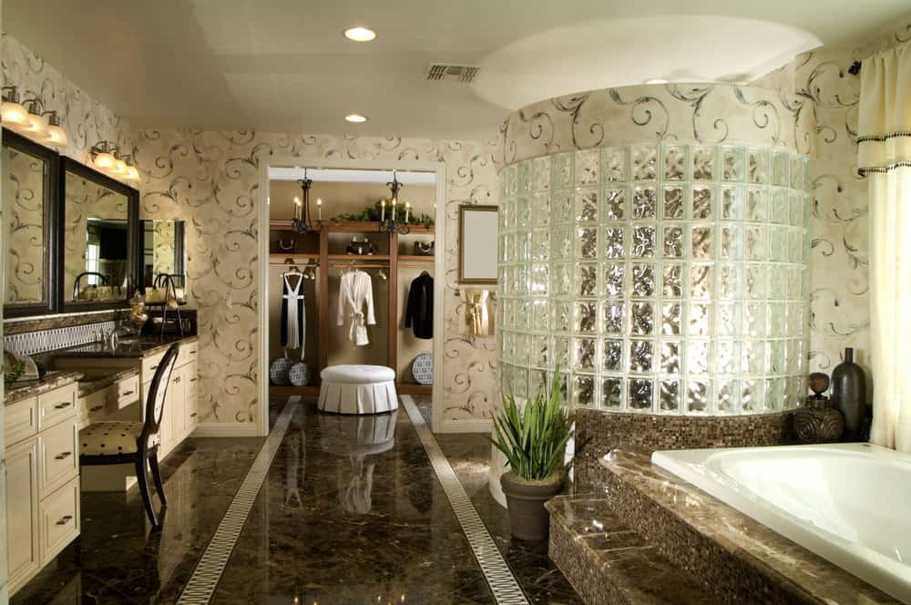 A primary bathroom surrounded by elegant walls and tiles floors. The walk-in shower room looks luxurious along with the drop-in tub on a marble platform.