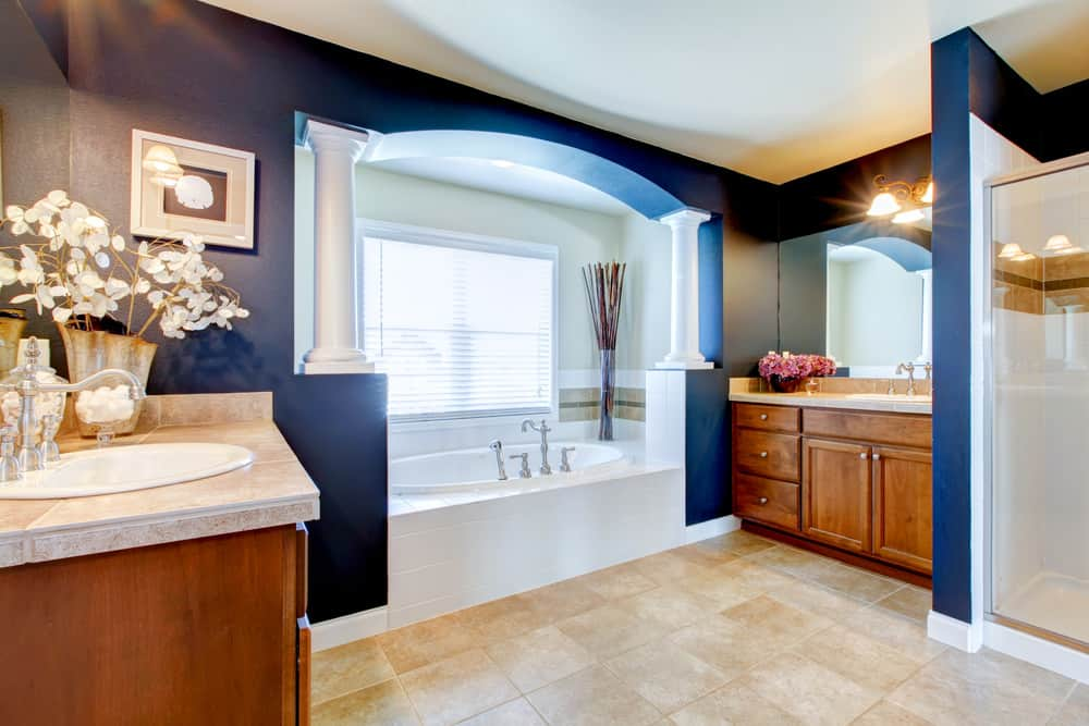 This alcove is flanked by small white pillars built into a navy blue accent wall flanked by wood vanities on each side.