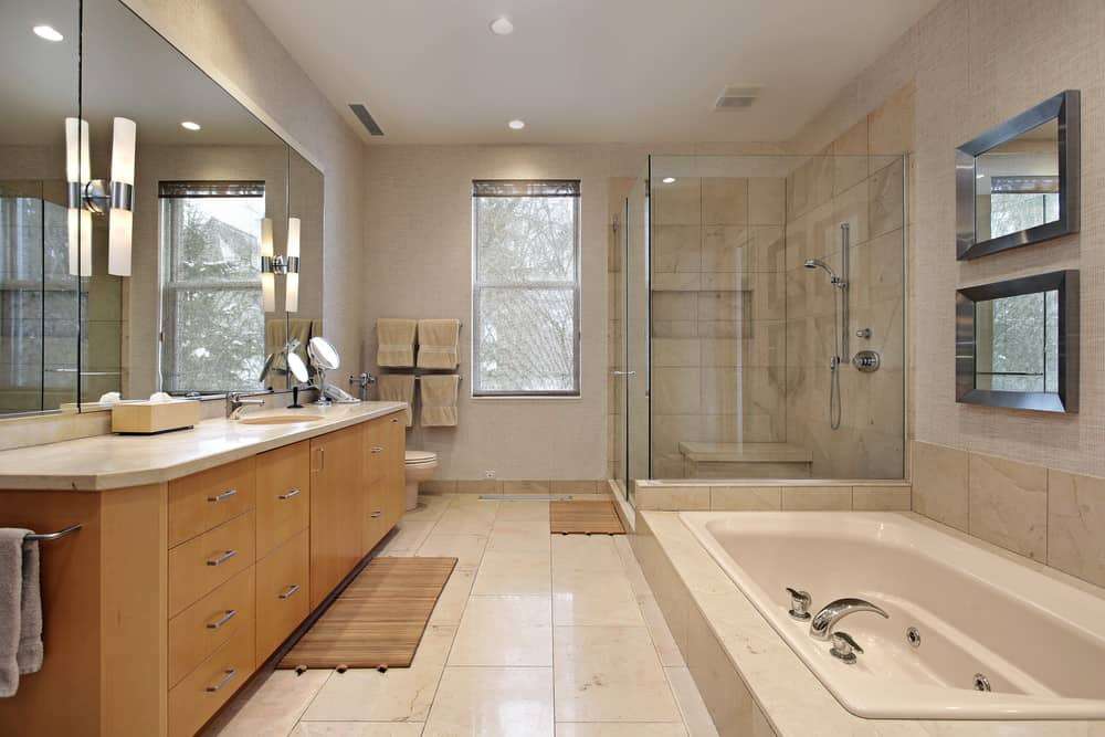 This master bathroom boasts a walk-in shower, a drop-in tub and a single sink. The room features tiles flooring and a regular ceiling.
