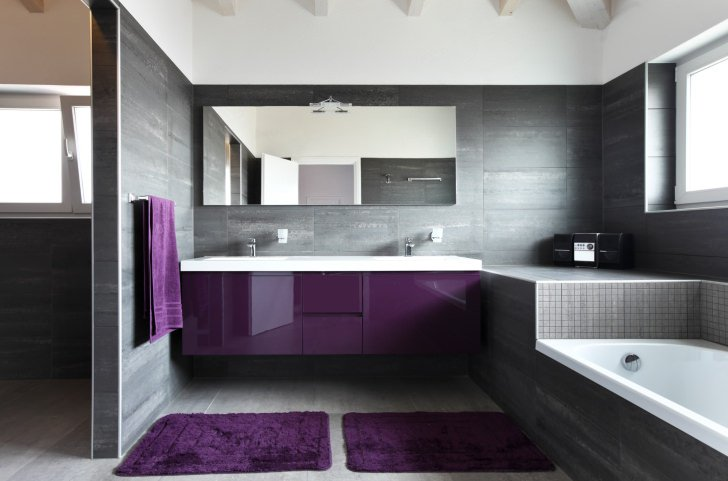 Contemporary primary bathroom with gray walls and floors along with a violet shade. The room offers a drop-in tub and a double sink on a floating vanity.