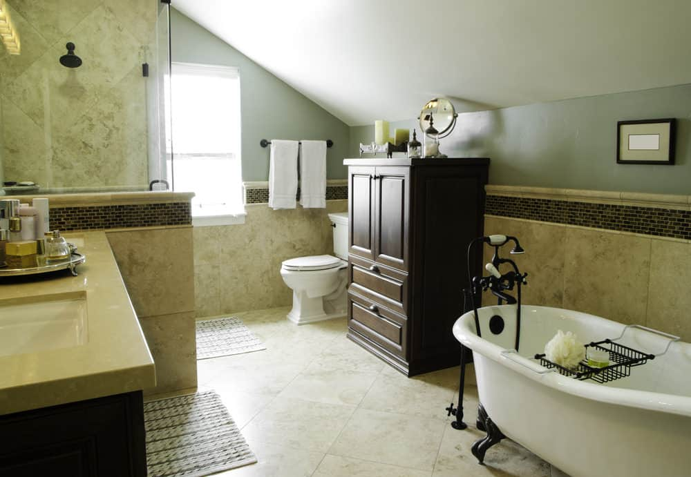 Medium-sized bathroom with classy tiles walls and floors. The room also features a freestanding tub and a shed ceiling.