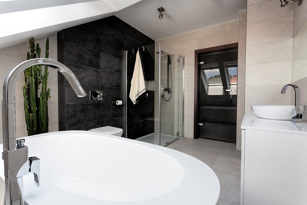 This master bathroom offers a walk-in shower with a stylish black wall. The room has a vessel sink and a freestanding tub.