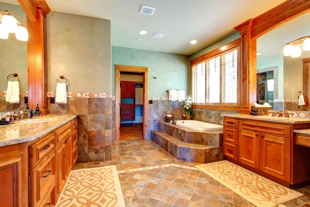 This primary bathroom boasts classy brown tiles flooring and a cherry accent. It also offers a deep soaking tub and charming sink counters.