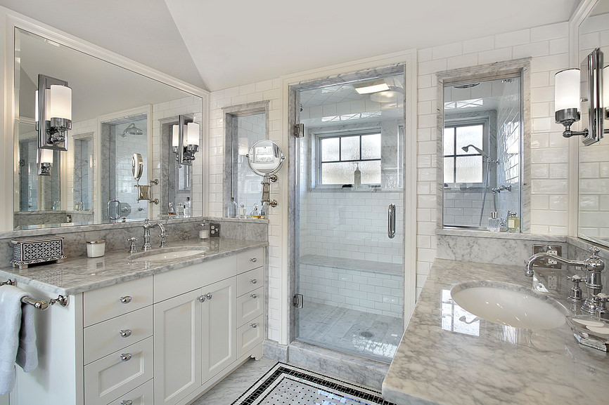 This creatively crafted master bathroom has a glimmer in every which direction due to the generously sized dual mirrors adjacent to each other and polished marbled flooring and countertops. Chrome faucets, handles, and lighting fixtures paired with the clear glass panel walk in shower enclosure to add a finishing sparkle.