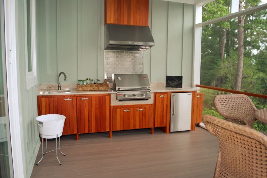 This deck features an outdoor kitchen with a wooden bar with a marble countertop.