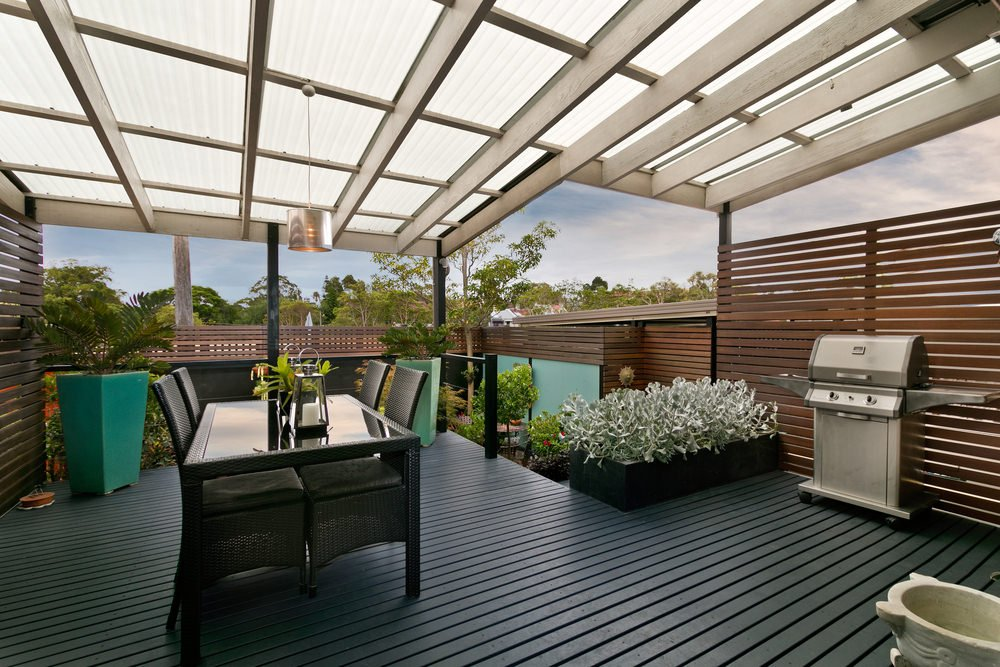This deck boasts a stylish dark finished flooring matching the plant's pots and the table set.