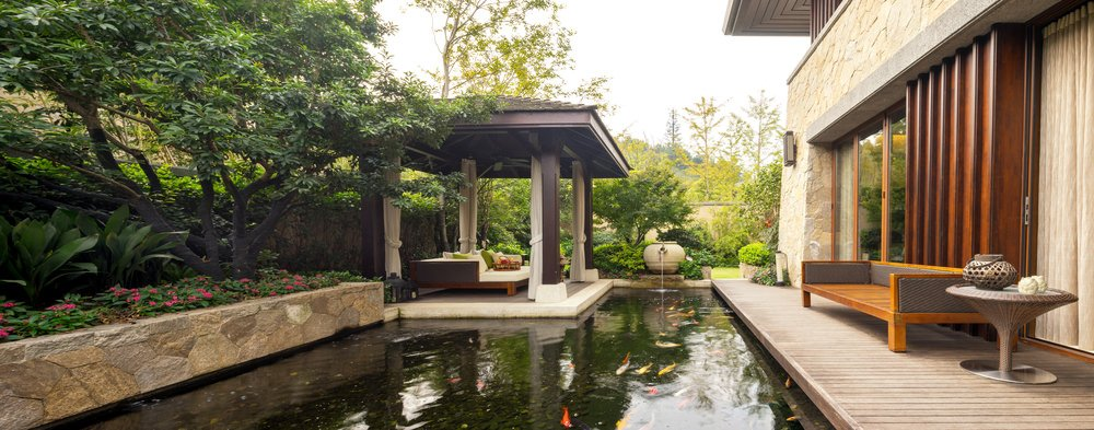 This deck features a comfortable seat with a side table. The pond full of colorful fishes looks glamorous.