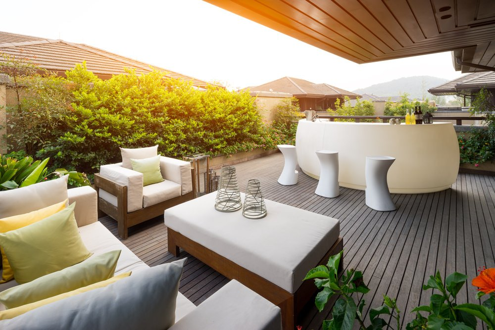 This deck features a white bar and stools. The chairs and table offers cushion seats and top along with a white sofa set with throw pillows.