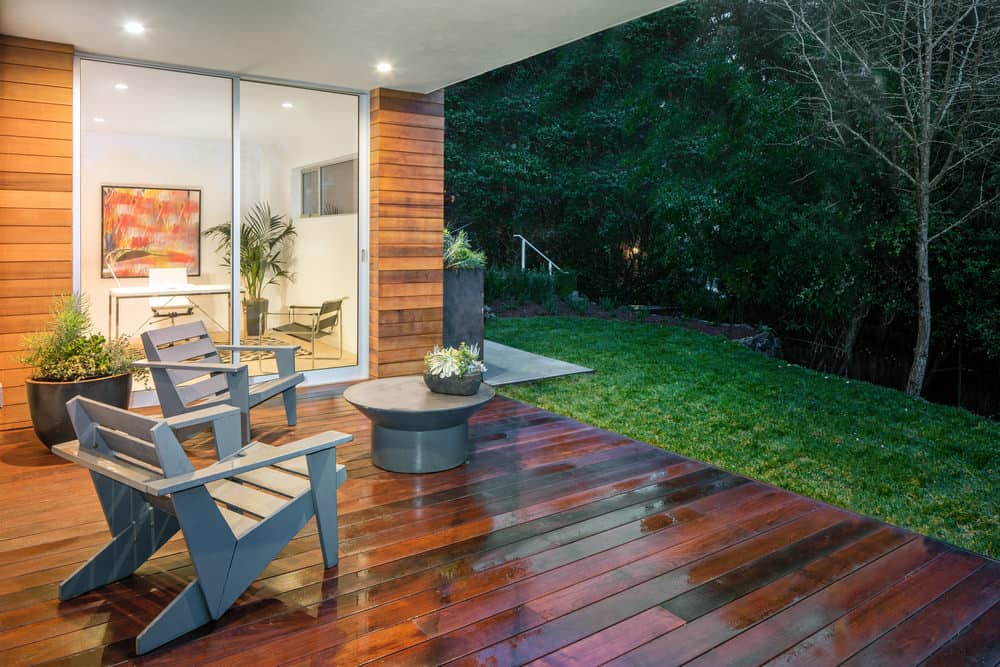 This modern deck features a couple of seats overlooking the gorgeous garden area and trees surrounding the property.