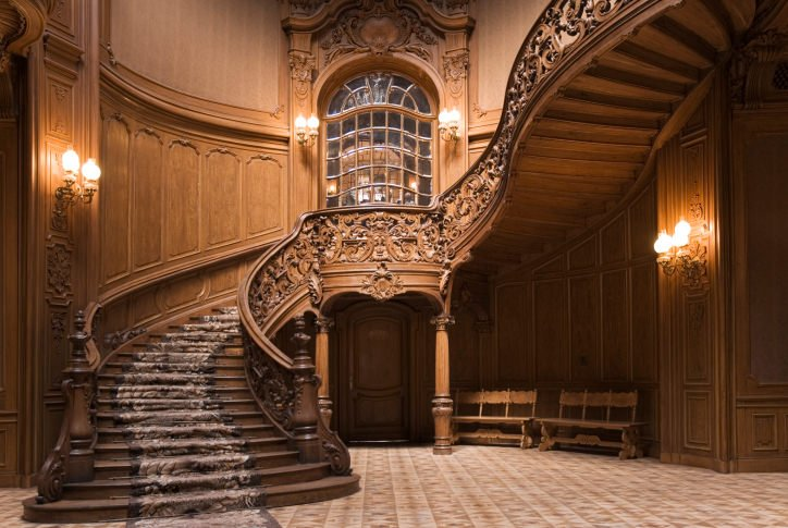 Magnificent foyer boasts a grand wooden staircase wrapped with a printed runner and framed with ornate balustrade that complements with the wall details.