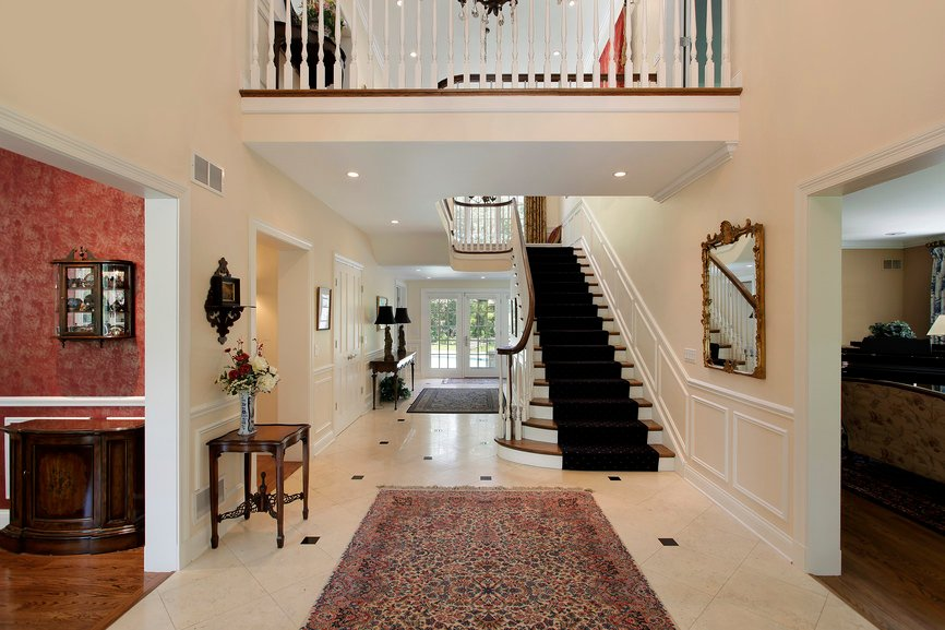 A classy home's entry with tiles floors and white walls. The staircase features black elegant carpet floors.