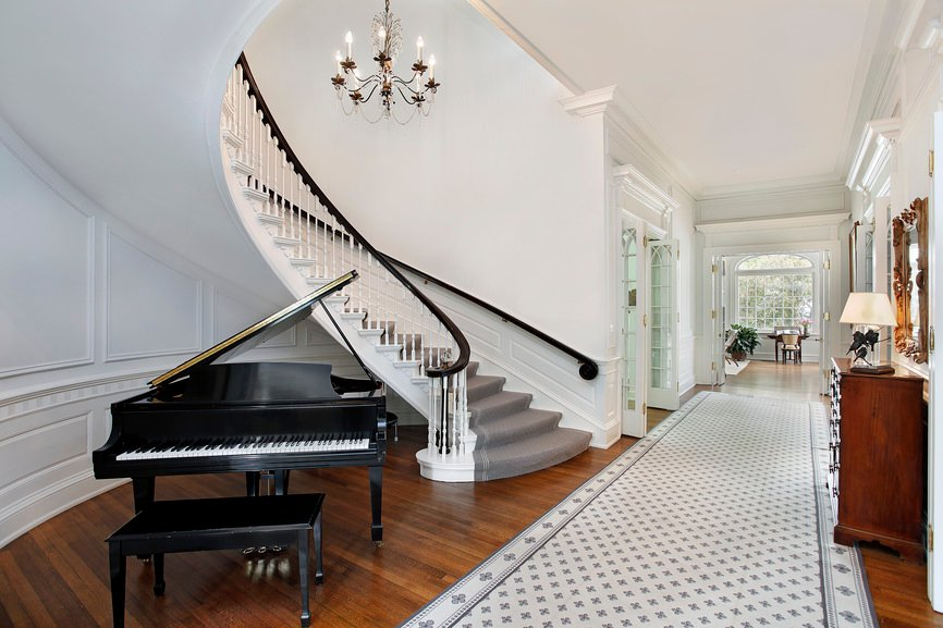 This home's entry boasts a curved staircase with gray carpet floors. There's also a black piano set on the home's hardwood flooring.