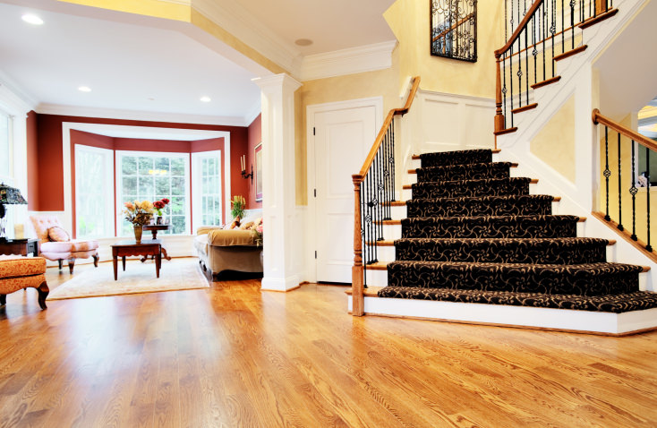This home's entry boasts a stunning staircase with glamorous carpet floors, black iron railings and wooden handrails.