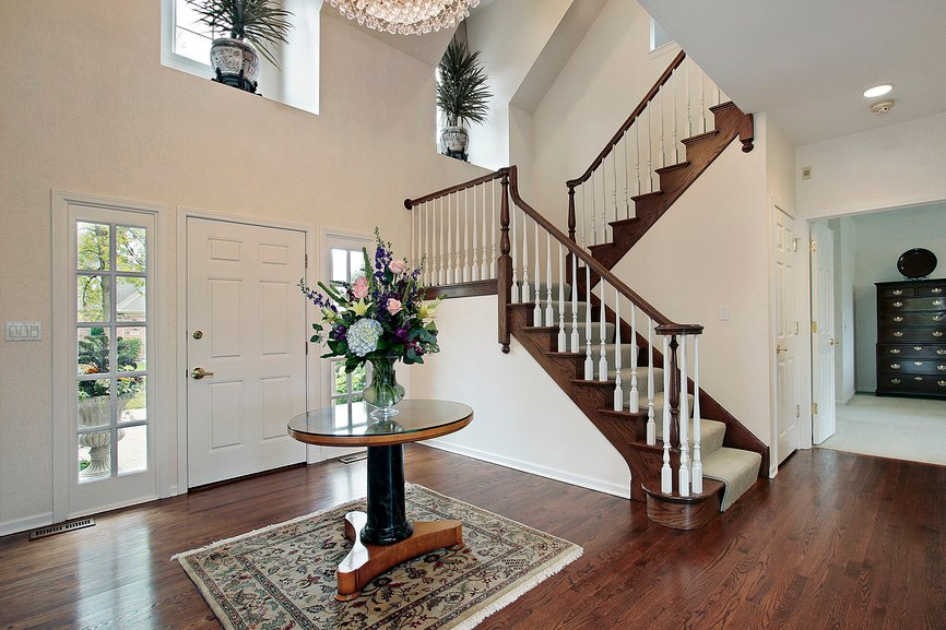 This home's entry features hardwood flooring and a centerpiece table set on a beautiful rug. The home also features an L-shaped staircase with carpet floors.