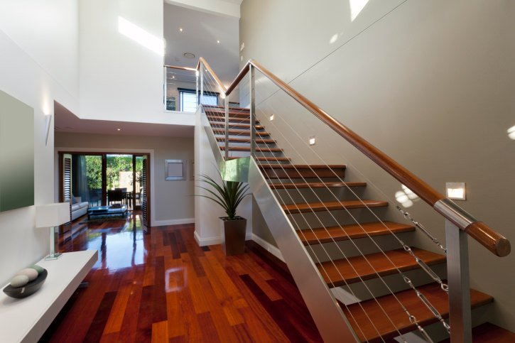 This glamorous modern foyer features a red hardwood flooring that steal every eyes away. The staircase itself is beautiful and matches well with the white walls and bench seating  on the side.