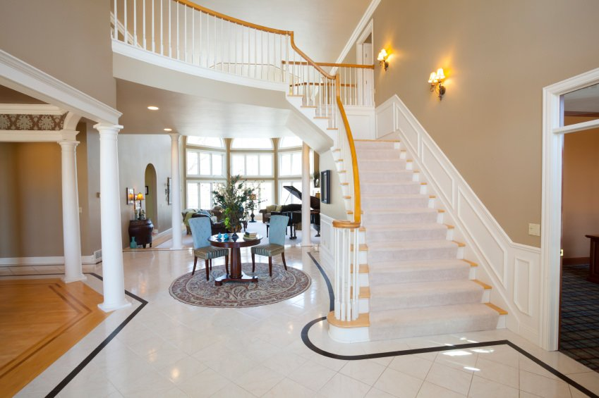 This elegant foyer features a beautiful staircase lighted by wall lighting. There's a coffee table set on a classy rug.