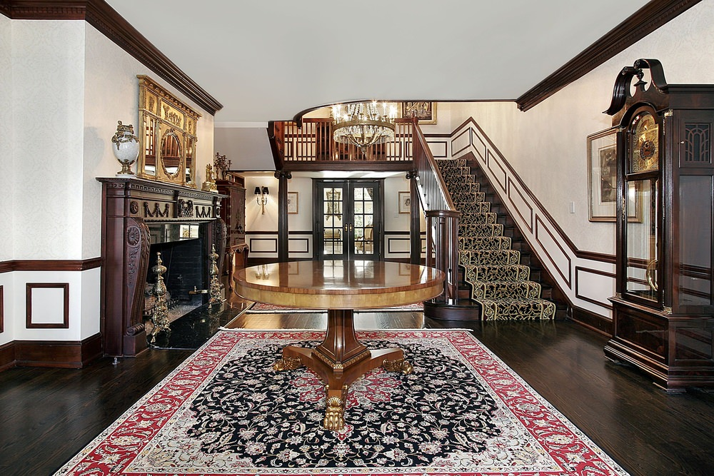 Classic foyer features a round wooden center table that sits on a red vintage rug and dark wood staircase dressed in elegant black stair runner.