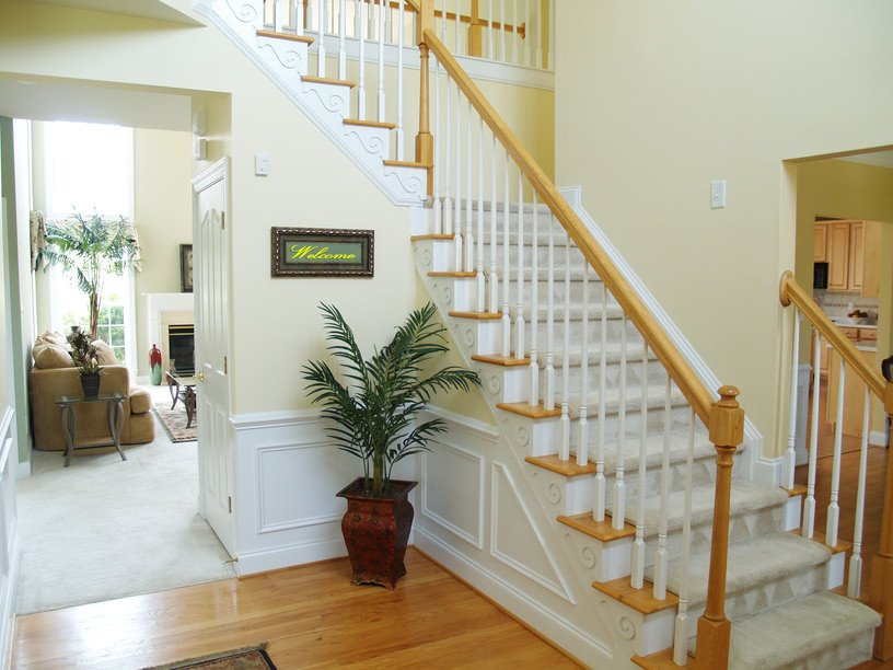 A foyer in a modern American home with a carpeted staircase, a view of the family room, and a prominent welcome sign.